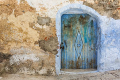 Grungy blue door in stone wall. Royalty Free Stock Image