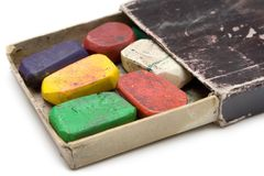 Grungy Box of Wax Crayons. Colorful wax crayons in an old box. Isolated on a white background Stock Photography