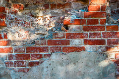 Grungy brick wall half covered with cement Stock Photo