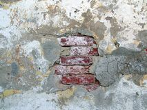 Grungy Bricks under old Stucco. The photo of artistic hole in the stucco stock photos