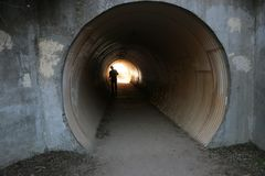 Silhouette of a man walking through a tunnel. Grungy cement walls frame the entrance to a tunnel and a man walking Stock Images