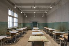 Grungy classroom in school. View to classroom with tables and small blackboard and grungy walls Stock Photo