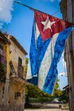 Grungy Cuban flag. Waving in a street of Old Havana with decaying buildings, Havana, Cuba royalty free stock photography