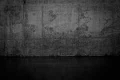Grungy dark concrete wall and wet floor Stock Images