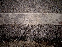Grungy, dirty view of asphalt. With distinct white stripe Stock Image