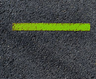Grungy, dirty view of asphalt with distinct green stripe Royalty Free Stock Photo