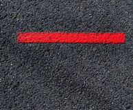 Grungy, dirty view of asphalt with distinct red stripe Stock Images