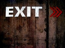 Grungy exit sign. Exit sign and arrows painted on a grungy old wall stock photos
