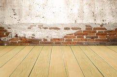 Grungy geweven rode baksteen en steenmuur met warme bruine houten vloer binnen oud veronachtzaamd en verlaten binnenland, metselw stock afbeelding