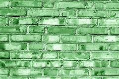 Grungy gräsplan tonad tegelstenhusvägg Arkivfoto
