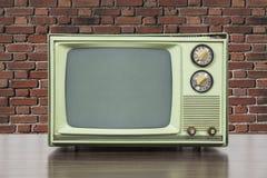 Grungy grünes Weinlese-Fernsehen mit alter Backsteinmauer Stockfotos