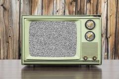 Grungy grünes Weinlese-Fernsehen mit hölzerner Wand und statischem Schirm Lizenzfreie Stockbilder