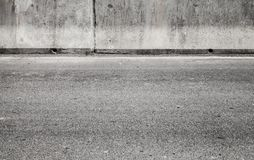 Grungy gray concrete wall and asphalt road stock photo