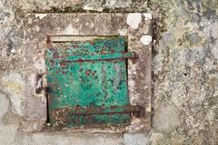 Grungy green metal door in gray concrete wall. Background photo texture Stock Image