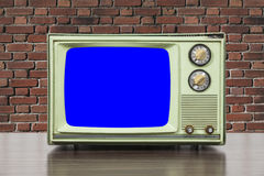 Grungy Green Vintage Television with Brick Wall and Chroma Key Blue Screen. Grungy green vintage television set with brick wall and chroma key blue screen Stock Photos