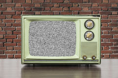 Grungy Green Vintage Television with Brick Wall and Static Scree. Grungy green vintage television set with brick wall and static screen Stock Photo