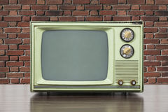 Grungy Green Vintage Television with Old Brick Wall. Grungy green vintage television set with brick wall Stock Photos