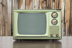 Grungy Green Vintage Television with Old Wood Paneling. Grungy green vintage television set with old wood paneling Royalty Free Stock Images