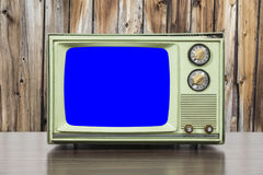 Grungy Green Vintage Television with Wood Wall and Chroma Key Bl. Grungy green vintage television set with wood wall and chroma key blue screen Royalty Free Stock Photography
