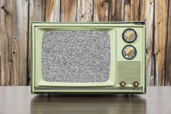 Grungy Green Vintage Television with Wood Wall and Static Screen. Grungy green vintage television set with wood wall and static screen Royalty Free Stock Images