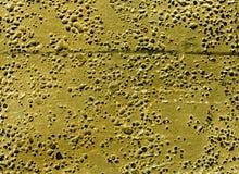 Grungy gul rubber yttersida med bubblor och skrapor Arkivfoto