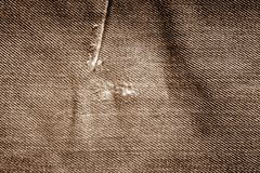 Grungy jeans cloth pattern in brown tone. Stock Images