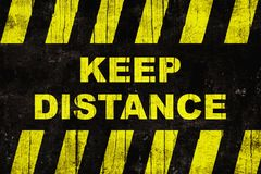 Keep distance text as warning sign with yellow and black stripes on painted wooden wall Stock Images