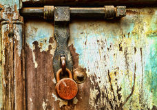 Grungy Locked Doors. A grungy locked doors sealing a closed wooden door Stock Photo