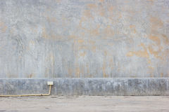 Grungy mud dirty concrete wall background with yellow PVC pipe o Stock Images