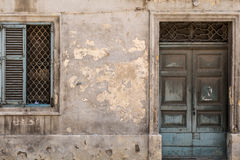 Grungy old door and window, Valletta, Malta. Traditional Maltese ancient wooden doorway and window with faded paint, shot straight-on in Valletta, Malta, Europe Stock Image