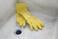 Grungy Old Sink. Grungy sink and rubber gloves Royalty Free Stock Images