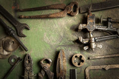 Grungy old tools. Grungy old metalwork tools on stained table background (processing cross-process stock images
