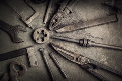 Grungy old tools. Grungy old metalwork tools on stained table background (processing cross-process stock photos