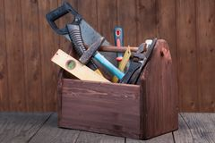 Grungy old tools on a wooden background front view. Royalty Free Stock Images
