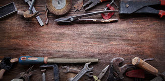 Grungy old tools on a wooden background stock image