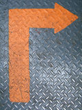 Grungy orange arrow. On a metallic background stock image