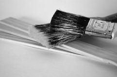 Grungy Paintbrushes on Paint Stirrers. Black and white image of two grubby, well-used paint brushes with three wooden paint stirrers.  Home improvement theme Stock Photo