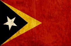 Grungy pappers- flagga av Östtimor vektor illustrationer