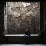 Grungy photo of lonely woman sitting at window in old building Royalty Free Stock Images