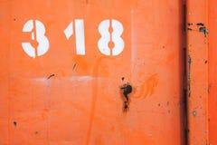 Grungy röd metallvägg med vitt nummer 318 Royaltyfri Bild
