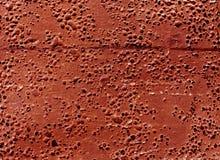 Grungy röd rubber yttersida med bubblor och skrapor Royaltyfri Foto