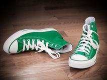 Grungy retro green sneakers. Retro green sneakers left on wooden floor grungy effects royalty free stock photo