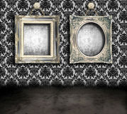 Grungy room with frames. Dark, grungy room with Victorian wallpaper and antique frames hanging by chains Royalty Free Stock Photo