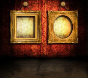 Grungy room with frames. Dark, grungy room with Victorian wallpaper and gold antique frames hanging by chains Stock Photos