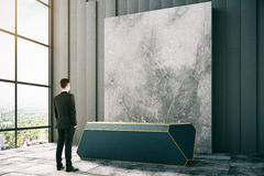 Grungy room with reception desk. Side view of abstract grungy concrete room with thoughtful businessman looking at reception desk and city view. Mock up, 3D Royalty Free Stock Photo