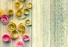 Grungy rustic background with paper spirals and swirls on a weat. Hered wooden table with copy space Royalty Free Stock Photos