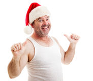 Grungy Santa Claus - This Guy. Scruffy unshaven middle-aged man in a santa hat and undershirt, smiling and pointing to himself with two thumbs. Isolated on white royalty free stock photography