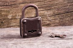 Grungy steel metal key and rusted lock on a old wooden boards ba Stock Images