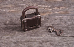 Grungy steel metal key and rusted lock on a old wooden boards background Royalty Free Stock Photography