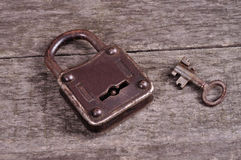 Grungy steel metal key and rusted lock on a old wooden boards background Stock Photography